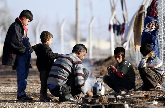 Syyrialaismies keittää teetä pakolaisleirillä Turkissa.