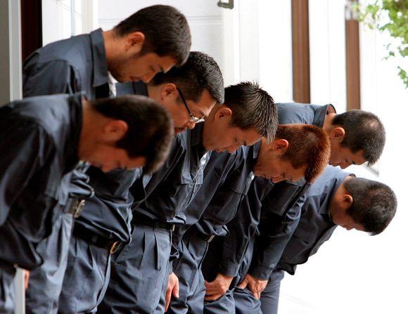 Seitsemän tummansinisiin paitoihin ja housuihin pukeutunutta japanilaista miestä rivissä päät painuksissa.
