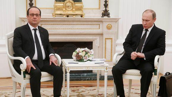 Hollande ja Putin istuvat tuoleilla koristeellisen takan edessä.