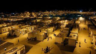 Syyrialaispakolaisten leiri Turkissa illalla, taivas on musta, lampuista leviää kellertävää valoa. Asumuksina ovat konttitalot, joita ulottuu horisonttiin saakka. Joillakin katoilla on pieniä lautasantenneja. Konttien välissä kulkevilla kaduilla kulkee siellä täällä ihmisiä.
