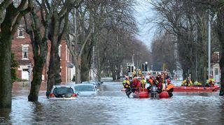 Vene jossa on pelastushenkilökuntaa kelluu tulvivalla tiellä.