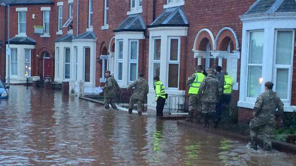 Sotilaita ja poliiseja kulkee talojen kivetyksiä pitkin välttääkseen astumasta tulvaveteen.
