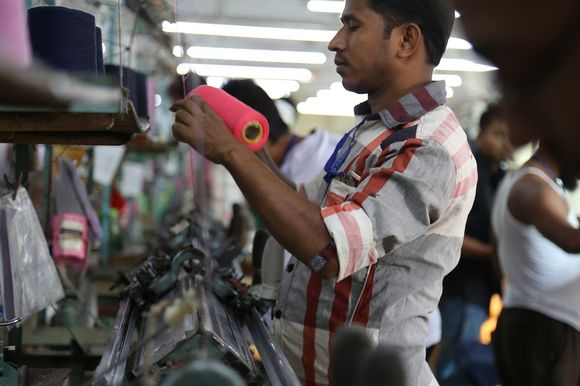 Mies käsittelee neuleisiin tarkoitettua lankaa tekstiilitehtaassa.