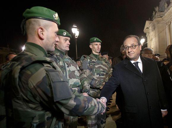 Ranskan presidentti Francois Hollande tervehtii turvallisuusjoukkoja Pariisissa uudenvuodenaattona 31. joulukuuta 2015.
