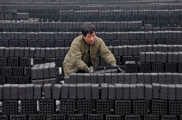 Vihreätakkinen kiinalainen työläinen lastaa hiilibrikettejä. Koko kuvan laajuudelta kulkee suoria rivejä tummia suoriin riveihin kasattuja hiilibrikettejä.