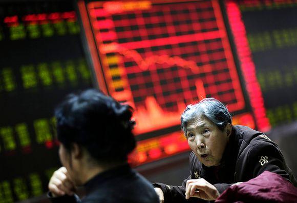 Kiinalaiset sijoittajat seuraavat pörssin kehtiystä infotauluilta Pekingissä.