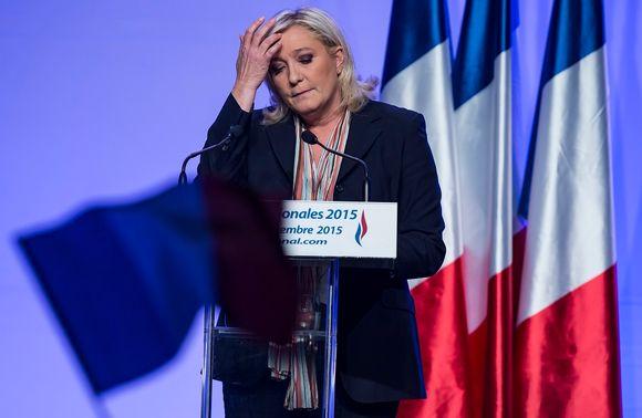 Marine Le Pen puhujalavalla, silmät kiinni, käsi otsalla. Taustalla Ranskan lippuja.