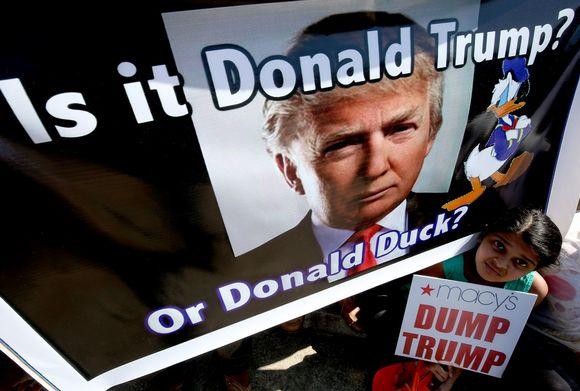 """Intialainen tyttö kurkistaa julisteen alta. Julisteessa on Donald Trumpin ja Aku Ankan kuvat ja kysymys: Is it Donald Trump or Donald Duck? Tytön kädessä kyltti riimittelee """"Dump Trump"""" eli tyhmä Trump."""