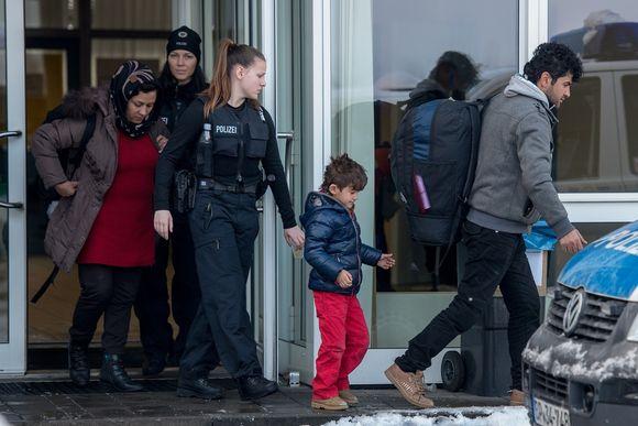 Kaksi naispoliisia ohjaa reppuselkäistä naista ja miestä ja pientä poikaa kadulla.