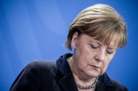Apean näköinen Angela Merkel katselee alaspäin.