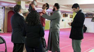 Iloisia ihmisiä moskeijassa. Mies pitelee vauvaa ilmassa.