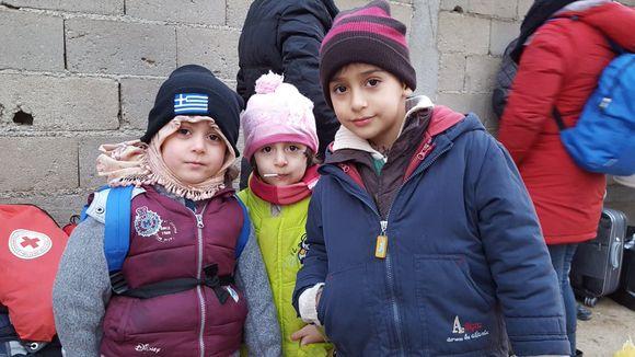 Kolme turvapaikanhakijalasta Preshevossa Serbiassa pipot ja talvitakit päällä.