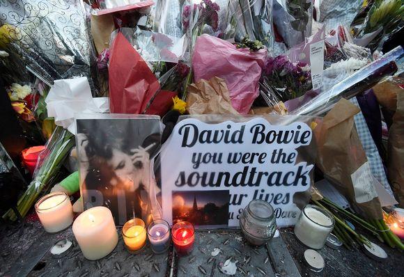 """Keko muovi- ja paperikääröissä olevia kukkia ja niiden edessä kyntilöitä. Bowien valokuvan vieressä iso kortti, jossa lukee englanniksi: """"David Bowie, olit elämämme elokuvan ääniraita""""."""