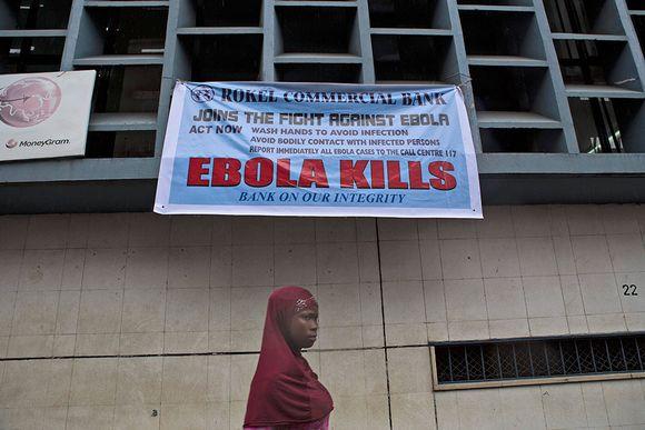 Nainen kävelee kadunvarteen ripustetun Ebolan varoitusjulisteen ohi Sierra Leonen pääkaupungissa Freetownissa.