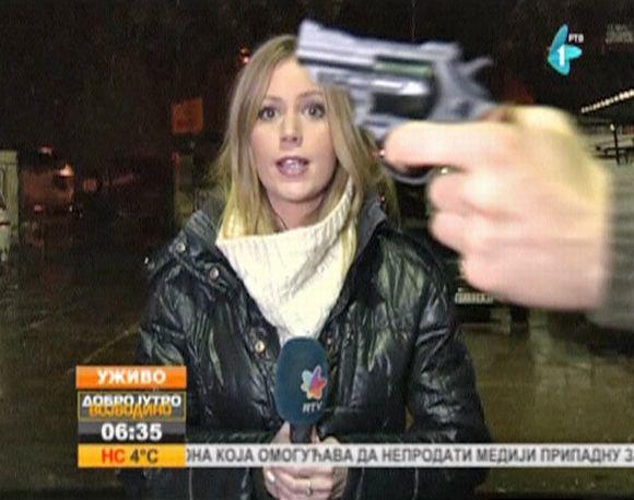 Video: Serbiassa kuvausryhmä teki perjantaina suoraa lähetystä kadulla, kun ohi kulkenut mies heilutti revolveria reportterin ja kameran välissä.