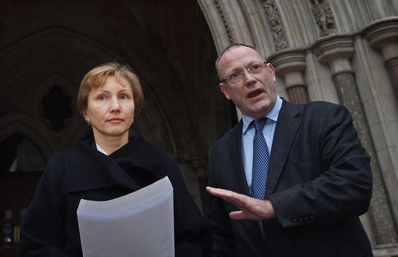 Aleksandr Litvinenkon leski Marina Litvinenko ja hänen asianajajansa Ben Emmerson seisovat Englannin ja Walesin Korkeimman oikeuden rakennuksen edessä Lontoossa. Emmerson puhuu ja korostaa sanojaan vasemmalla kädellään. Marina Litvinenko pitää kädessään paperia, josta on lukenut lausuntonsa. Litvinenko on pukeutunu mustaan asuun, joka uppoaa tummaan taustaan.