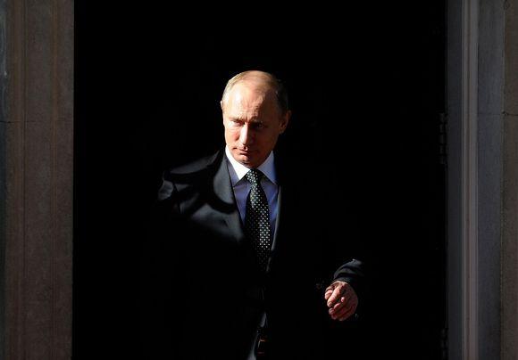 Vladimir Putin mustaa taustaa vasten. Aurinko valaisee Putinin kasvojen toisen puolen, toinen on varjossa.