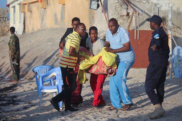 Uhria kannetaan pois rannalta Somalian pääkaupungissa Mogadishussa, jossa alkoi piiritystilanne torstai-iltana. Tilanne päättyi aikaisin aamulla poliisin rynnäkköön.