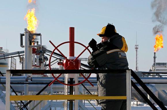 Öljyntuotantoa kuvaava arkistokuva, joka on päivätty 21. helmikuuta 2007. Öljytyöläinen pyörittää punaista ohjausratasta öljyntuotantolaitoksella Priobskojen öljykentällä. Taustalla loimuavat kaasunpoistoliekit. Taivas on vaaleansininen. Työläisellä on keltainen kypärä ja paksunnäköinen työtakki. Miehen takin selässä lukee Rosneft.