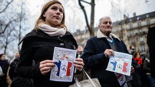 Nainen ja mies plakaatit käsissään