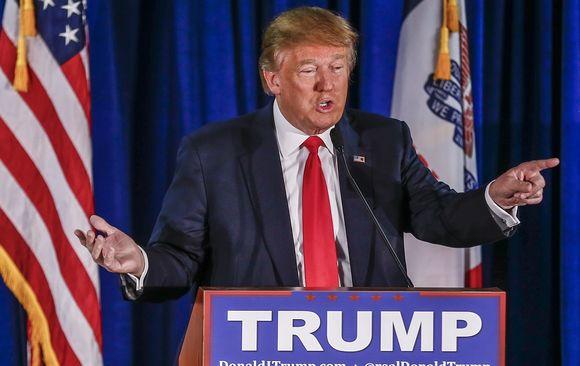 Donald Trump puhuu viittilöiden käsillään. Taustalla näkyy Yhdysvaltain lippu. Trumpilla on tumma puku, kirkkaanpunainen kravatti. Puhujankorokkeessa lukee isoilla valkoisilla kirjaimilla sinisellä pohjalla 'TRUMP'.