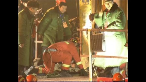 Video: Miehiä kurkistelee aukkoon, josta kaivosmiestä nostetaan.