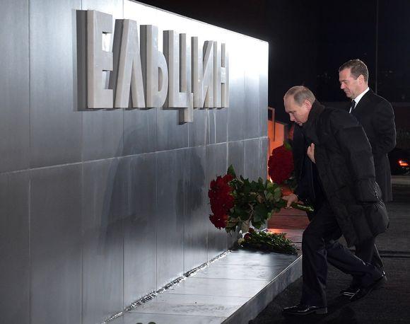 """Putin ja Medvedev laskevat punaisia ruusuja metallisen seinämän eteen. Seinämässä lukee suurilla kohokirjaimilla """"Jeltsin""""."""