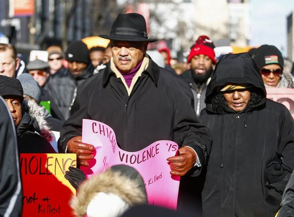Jesse Jackson ja muita talvipukuisia, vakavailmeisiä mielenosoittajia.