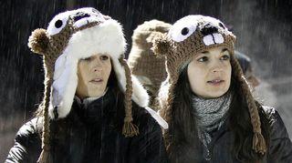 Kaksi nuorta naista sateessa, päässä murmelinnaamahatut.