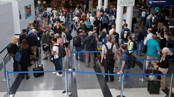 Ihmiä laukkuineen kiemurtelevassa jonossa terminaalin sisällä.
