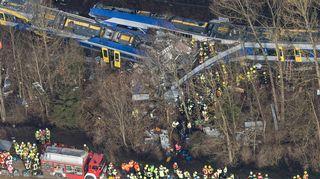 Ilmakuvassa näkyy kaksi toisiinsa törmännyttä junaa ja keltaliivisiä ja punatakkisia pelastustyöntekijöitä tuhon keskellä. Radan vierellä kulkevalla tiellä on paloauto.