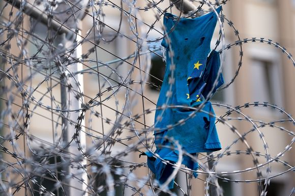 Revitty EU-lippu piikkilanka-aidan takana