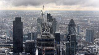 Lontoon taivaanrannassa näkyy uhkaavia pilviä. Edessä rakenteilla olevia pilvenpiirtäjiä.