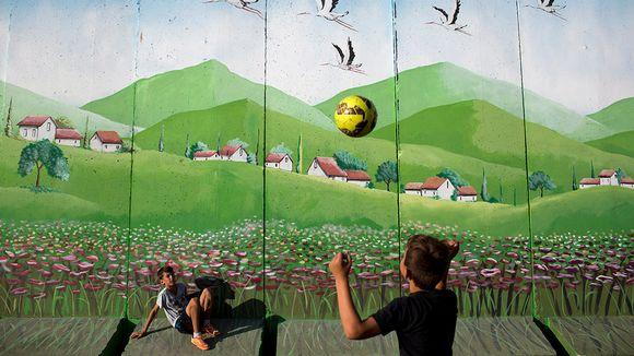 Israelilaisia koululaisia pelaamassa palloa koulun pihalla suojamuurin vieressä.