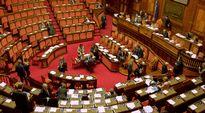 Kuvassa senaatin istuntohuone, jossa punaiset kokolattiamatot ja korkealle nouseva penkkirivistö. Edustajia keskustelemassa senaatin istuntosalin keskellä.