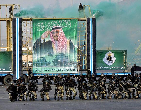 Saudien erikoisjoukkoja on kahdessa rivissä suuren julisteen edessä. Sotilailla on kädessään rynnäkkökivääreitä, yllään mustat paidat, maastokuvioidut housut, kypärät, suojalasit ja kasvonaamiot. Julisteessa taustalla on kuva prinssi Mohammed bin Naif Abdulazizista, joka on maan sisäministeri.