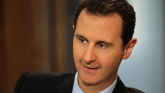 Syyrian presidentti Bashar al-Assad hymyilee. Hänellä on tumma puku.