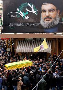 Suuri väkijoukko kuljettaa keltaiseen kankaaseen käärittyä arkkua. Arkun edellä kulkee keltainen lippu, jossa on miehen kasvokuva. Saattue ohittaa Hizbollahin johtajaa esittävää suurta julistetta.