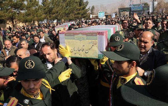 Vihreäpukuiset sotilaat kantavat arkkua. Arkkua ympäröi tiivis väkijoukko. Kauempana näkyy puita. Väkijoukon keskellä taaempana näkyy myös toinen arkku.