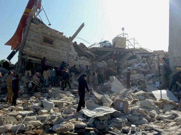 Ihmisiä kulkee pahoin tuhoutuneen rakennuksen raunioilla.