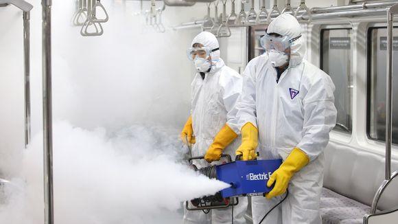 Kaksi valkoisiin suojahaalareihin pukeutunutta työntekijää levittää savuavaa hyönteismyrkkyä junavaunuun.