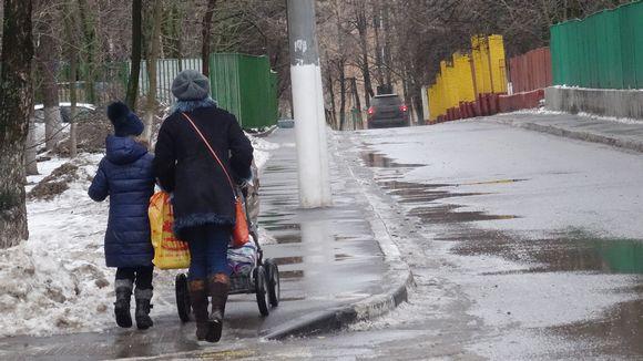 Äiti lapsineen kulkee kadulla.