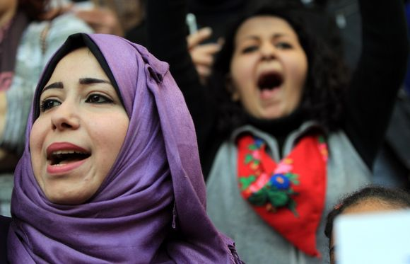 Kaksi naista huutaa iskulauseita mielenosoituksessa.