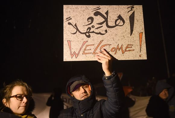 Kaksi mielenosoittajaa pimeässä illassa. Toinen pitelee koholla tervetuloa-kylttiä.