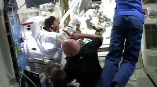 Kuvassa Scott Kelly ja Sergei Volkov auttavat Timothy Kopraa kansainvälisellä avaruusasemalla.