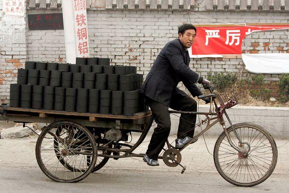 mies ajaa hiilikuormaa pyörällään