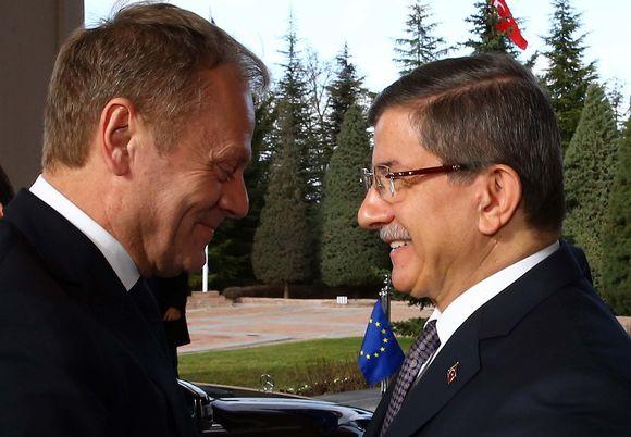 Hymyilevät Tusk ja Davutoğlu kasvokkain. Taustalla auto, jonka keulassa liehuu EU:n lippu.