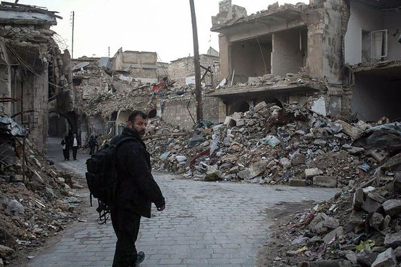 Rami Adham kävelee kadulla, jota reunustavat raunioituneet talot.