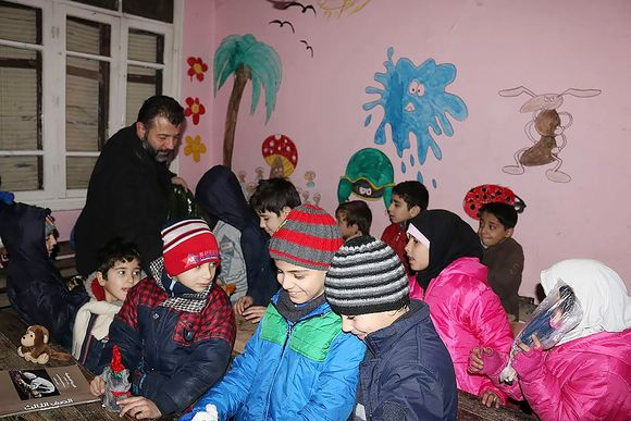 Rami Adham jakaa luokkahuoneessa lelula talvipukuisille lapsille.