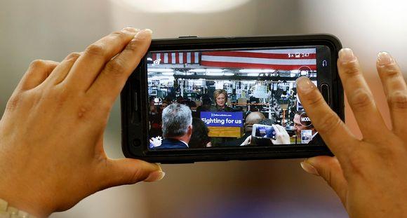 Naisen kädet pitelevät kännykkää, jolle tallentuu videota puhujapöntössä olevasta Hillary Clintonista.